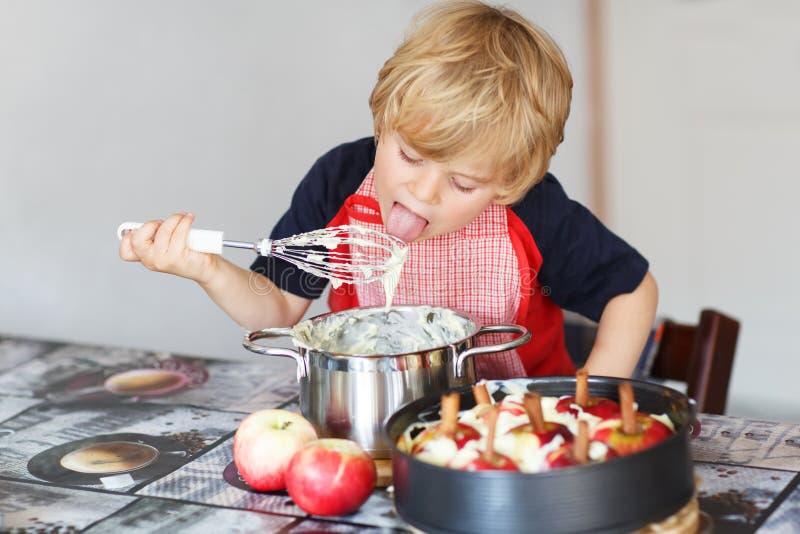 Helfender und backender Apfelkuchen des entzückenden kleinen Jungen in Haupt'' s-kitc lizenzfreie stockfotos