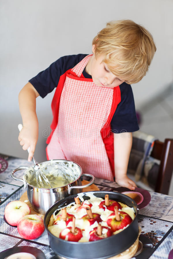 Helfender und backender Apfelkuchen des entzückenden kleinen Jungen in Haupt'' s-kitc stockbilder