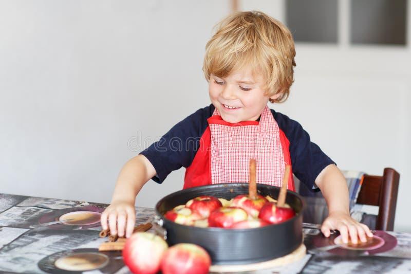 Helfender und backender Apfelkuchen des entzückenden kleinen Jungen in Haupt'' s-kitc stockfotos