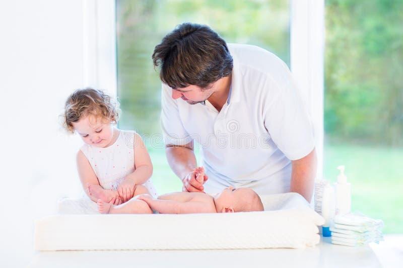 Helfender Vater des entzückenden Kleinkindmädchens, zum der Windel zu ändern lizenzfreie stockbilder