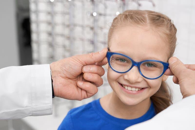 Helfendes Mädchen Doktoraugenarztes, zum von Brillen zu wählen stockfotos