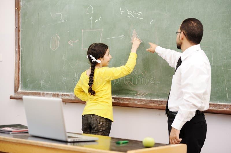 Helfendes Schulmädchen des Lehrers lizenzfreies stockbild