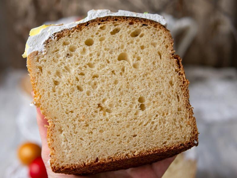 Helft-besnoeiing eigengemaakt zoet Pasen-brood in de handen van de vrouw van een bakker Plak van het orthodoxe zoete brood van Pa royalty-vrije stock fotografie