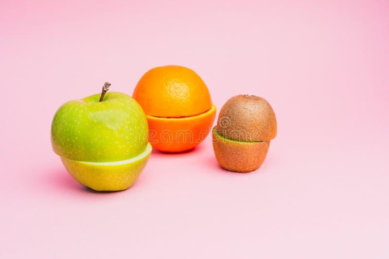 Helft-besnoeiing vruchten: een groene appel, een sinaasappel en een kiwi op een pastelkleur doorboren achtergrond royalty-vrije stock foto