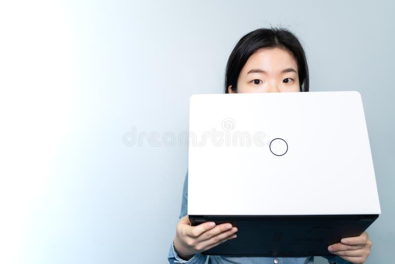 Helft die van Aziatisch bedrijfsvrouwengezicht, laptop over BLAUWE hemelachtergrond de houden met de ruimte van de exemplaartekst royalty-vrije stock afbeelding