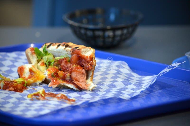 Helft-gegeten hotdogbroodje met specerijen op een blauw dienblad stock afbeeldingen