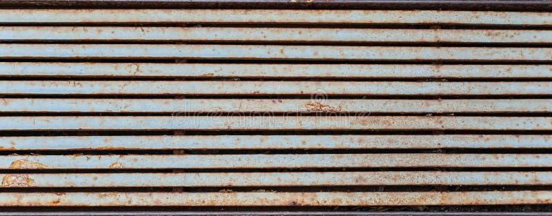 Helft-geroest regenvalrooster die als horizontale metaalstrepen kijken stock foto