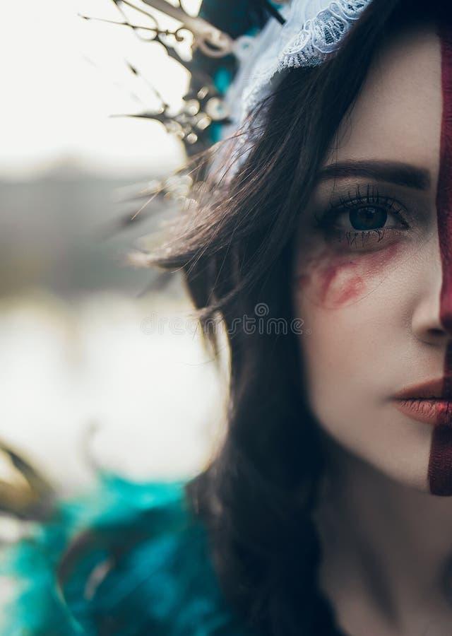 Helft-gezicht portret van jonge vrouw in het beeld van een fee en een tovenares stock fotografie