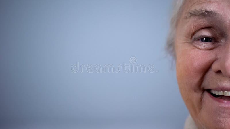 Helft-gezicht van positief bejaard wijfje op grijze achtergrond, vrolijke gepensioneerde stock foto