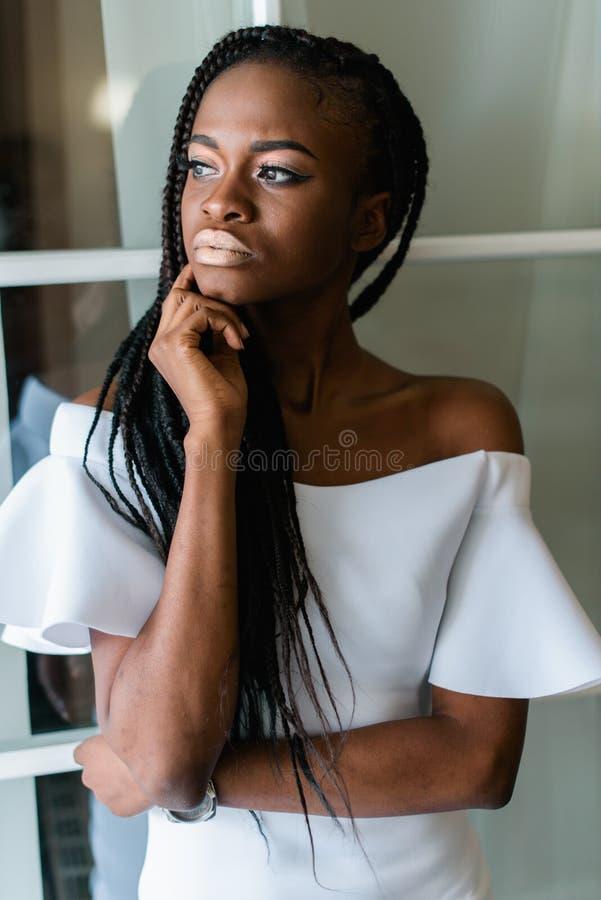 Helft-lengte portret van de mooie elegante Afrikaanse dame die in witte kleding opzij kijken Binnenplaats royalty-vrije stock foto