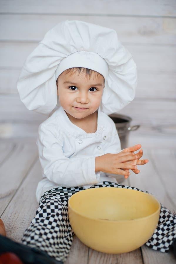 Helft-lengte portret van een kleine chef-kok Leuk bekijkt weinig kind in schort en chef-kokhoed camera stock afbeelding