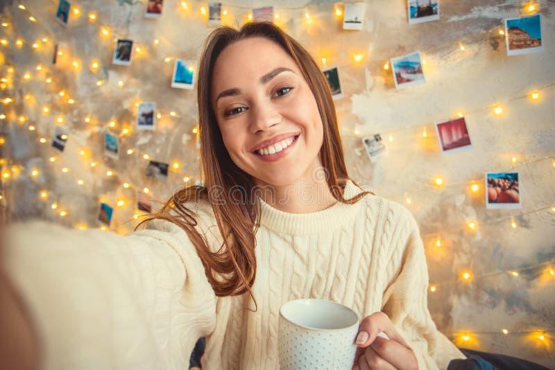 Helgen för den unga kvinnan dekorerade hemma sovrummet som tar selfiefoto royaltyfri foto