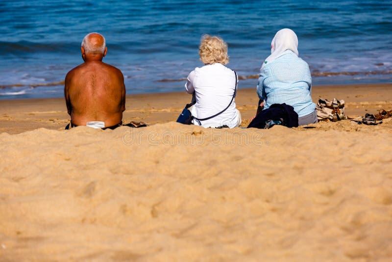 Helgon-Jean de Luze, Frankrike - Sept 28, 2016: familjsammanträde på strandhanddukar i sanden Tre personer, en man och två kvinno arkivbild
