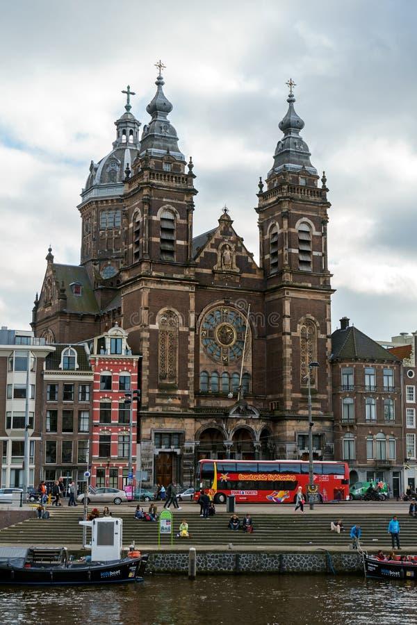 Helgon Nicholas Basilica den viktiga katolska kyrkan i det gamla mittområdet och typiska holländska hus, Amsterdam, Nederländerna royaltyfria bilder