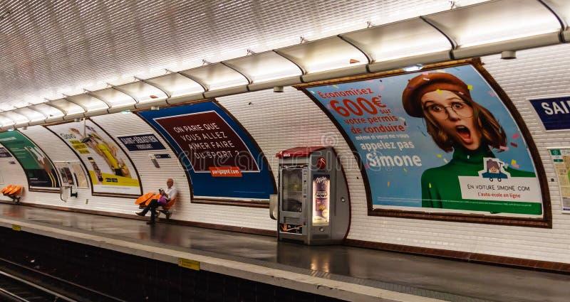 Helgon Sebastien Parisisk gångtunnelstation med passageraren och annonseringsaffischer arkivbild