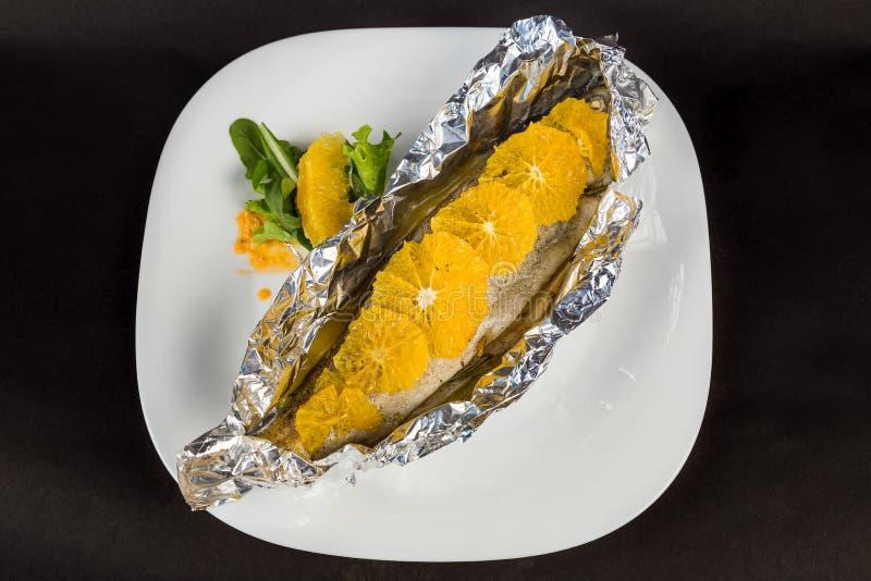 Helhet grillad fisk i folie med apelsiner som tjänas som örter royaltyfri fotografi
