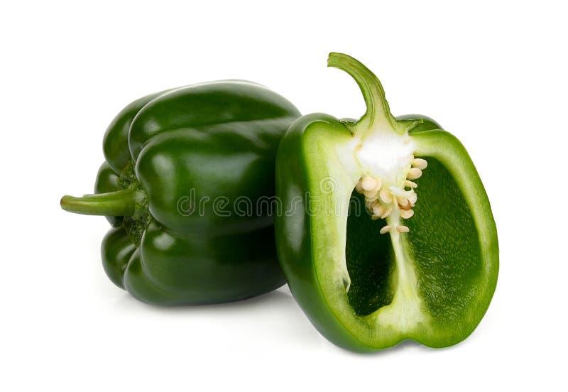 Helhet och halv grön spansk peppar som isoleras på vit arkivfoton