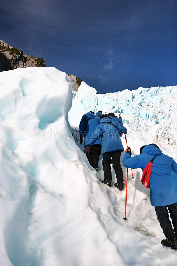 Hikers in single file ascending rugged icy slope at glacier exploration royalty free stock images