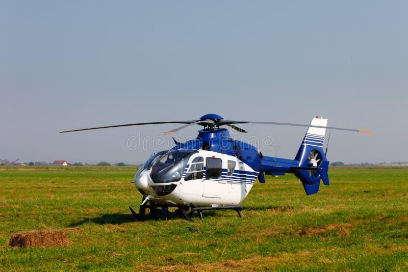 Helicóptero azul no campo imagem de stock royalty free