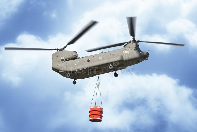 Helicóptero da luta contra o incêndio do voo italiano do exército com uma cubeta vazia do metal para extinguir um fogo fotos de stock