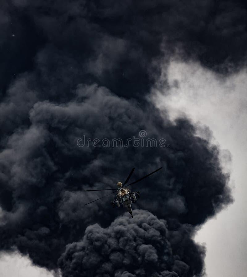 Helicóptero de ataque en el fondo del humo después de la misión Helicóptero ruso de ataque moderno con armas foto de archivo libre de regalías