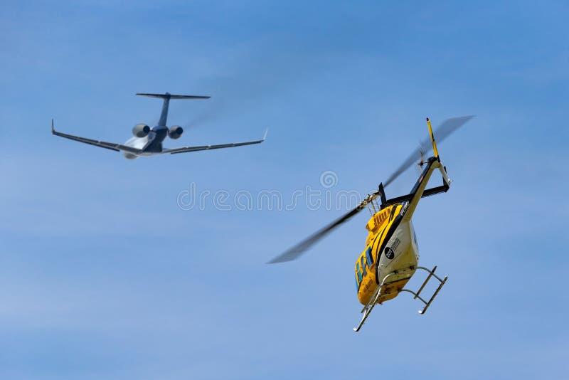 Helicóptero de Bell 206L-1 LongRanger II G-LIMO dos helicópteros da elite que decola com um jato do negócio no fundo imagens de stock
