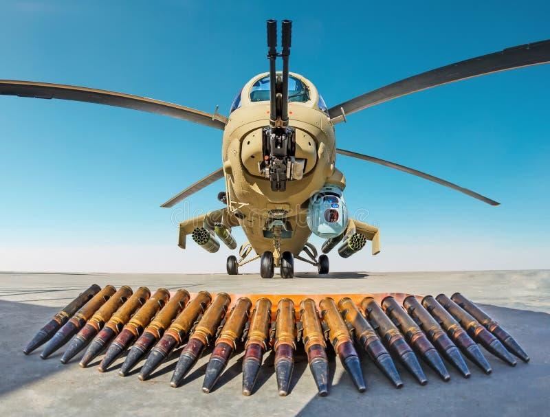 Helicóptero de combate militar com escudos da munição na terra foto de stock