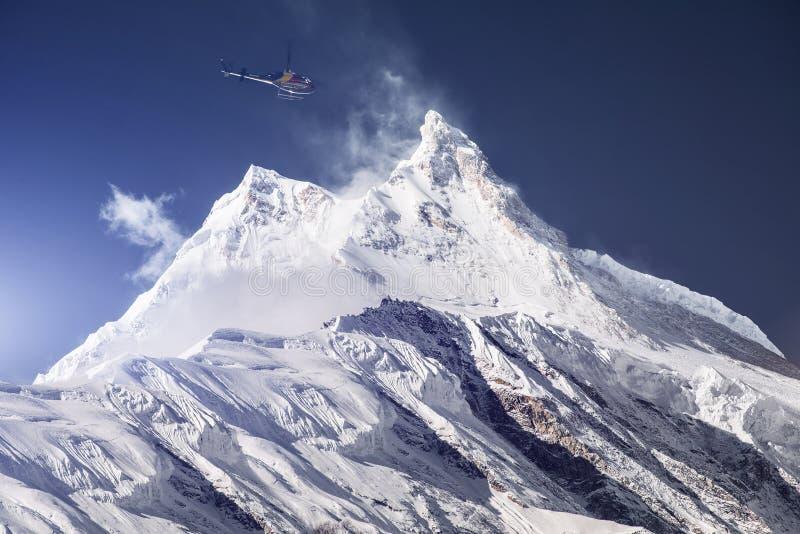 Helicóptero do salvamento sobre o pico de montanha nevado fotografia de stock