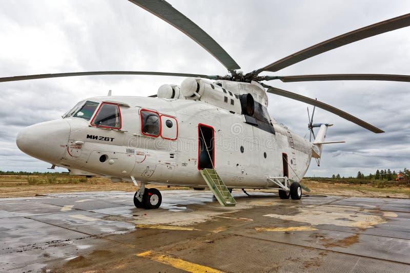 Helicóptero do transporte de Mi-26T O mundo o maior e helicóptero suportando a carga estacionado no aeroporto na vila de Urengoy  fotos de stock