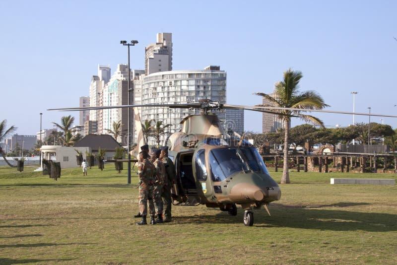 Helicóptero e pessoal militar na parte dianteira da praia imagem de stock