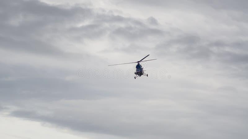 Helicóptero en cielo nublado imagenes de archivo