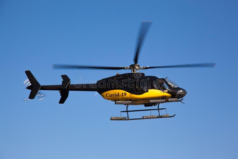 Helicóptero negro y amarillo con la inscripción covid-19 Helicóptero contra el cielo azul en Nueva York EE.UU. El concepto de foto de archivo