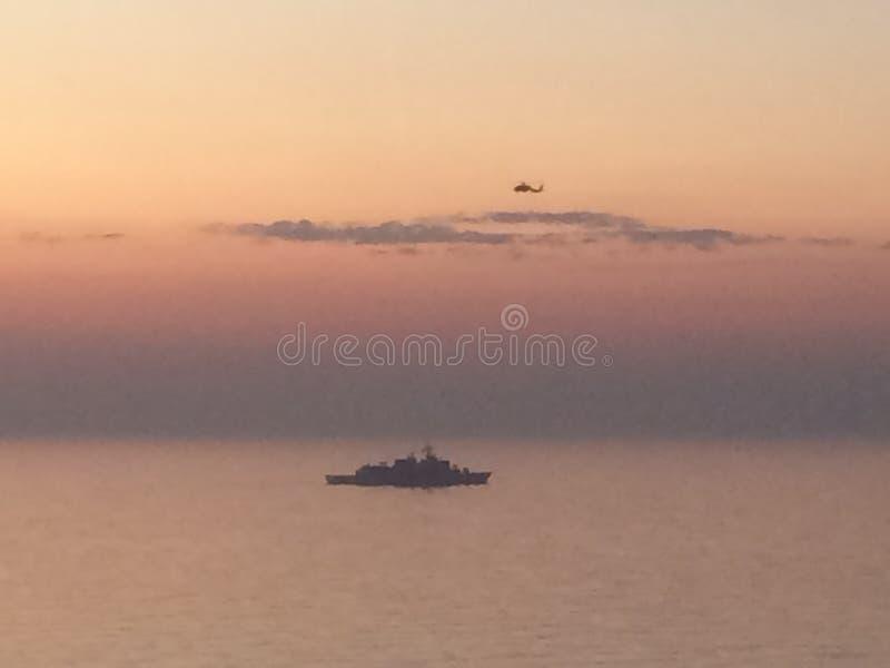 Helicóptero que paira sobre um navio de guerra no mar Mediterrâneo fotos de stock royalty free