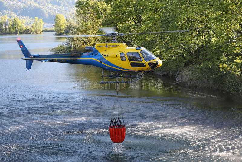 Helicóptero que pegara a água durante operações da luta contra o incêndio imagens de stock