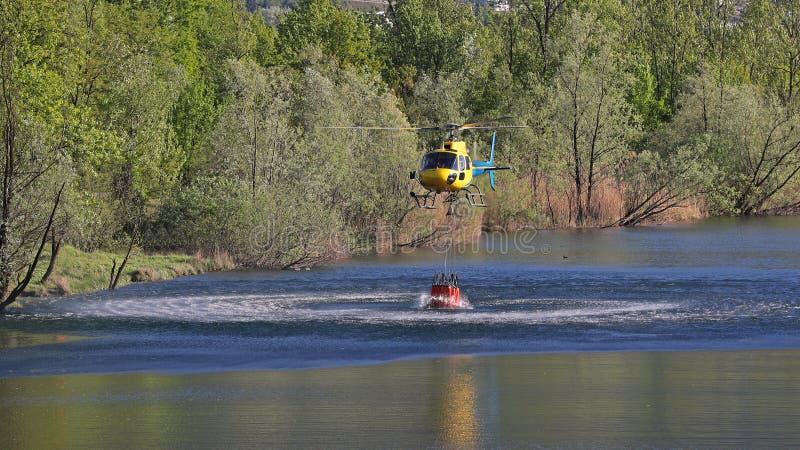 Helicóptero que pegara a água durante operações da luta contra o incêndio fotos de stock