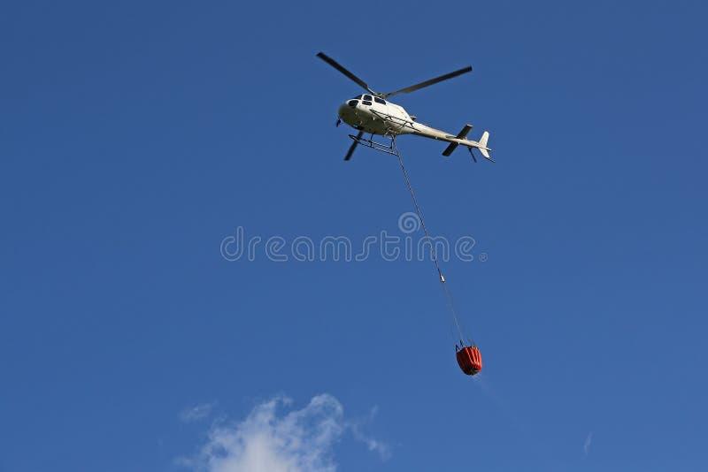 Helicóptero que pegara a água durante operações da luta contra o incêndio fotografia de stock