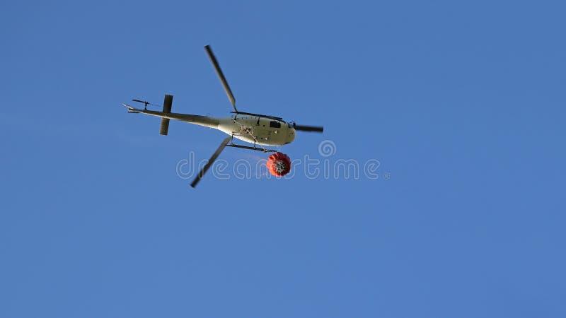 Helicóptero que pegara a água durante operações da luta contra o incêndio foto de stock royalty free