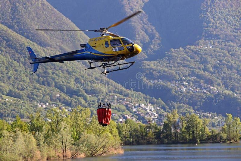 Helicóptero que pegara a água durante operações da luta contra o incêndio fotografia de stock royalty free