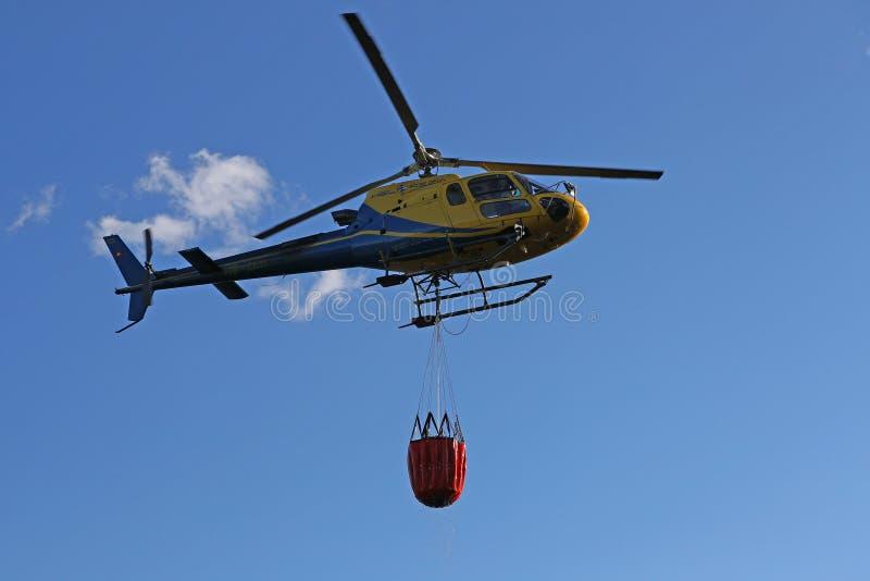 Helicóptero que pegara a água durante operações da luta contra o incêndio imagens de stock royalty free