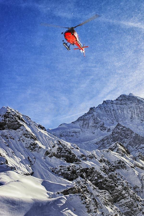 Helicóptero rojo en el cielo suizo de las montañas cerca de la montaña de Jungfrau fotos de archivo libres de regalías