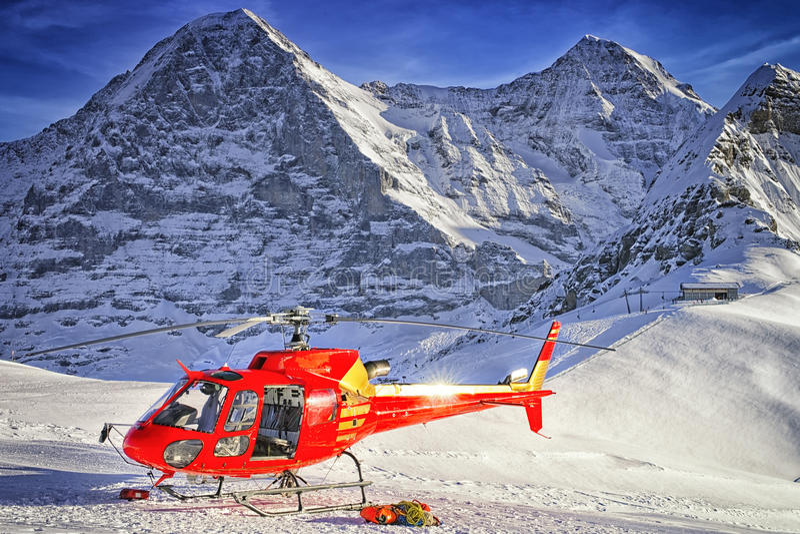 Helicóptero vermelho na estância de esqui suíça perto da montanha de Jungfrau fotos de stock