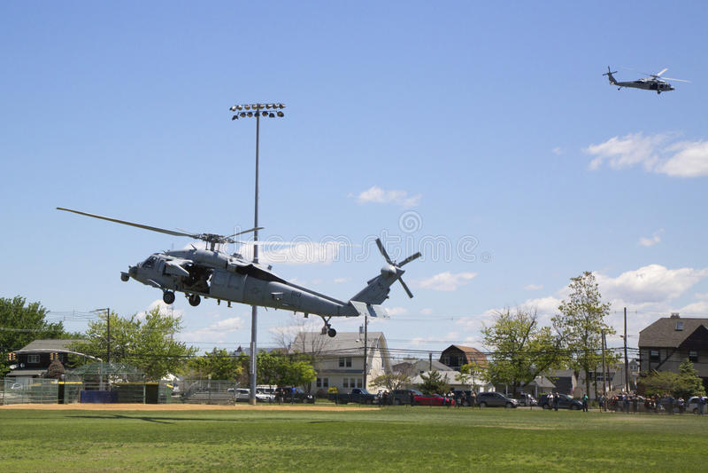 Helicópteros de MH-60S de la escuadrilla cinco del combate del mar del helicóptero con el aterrizaje del equipo del EOD de la mar fotografía de archivo