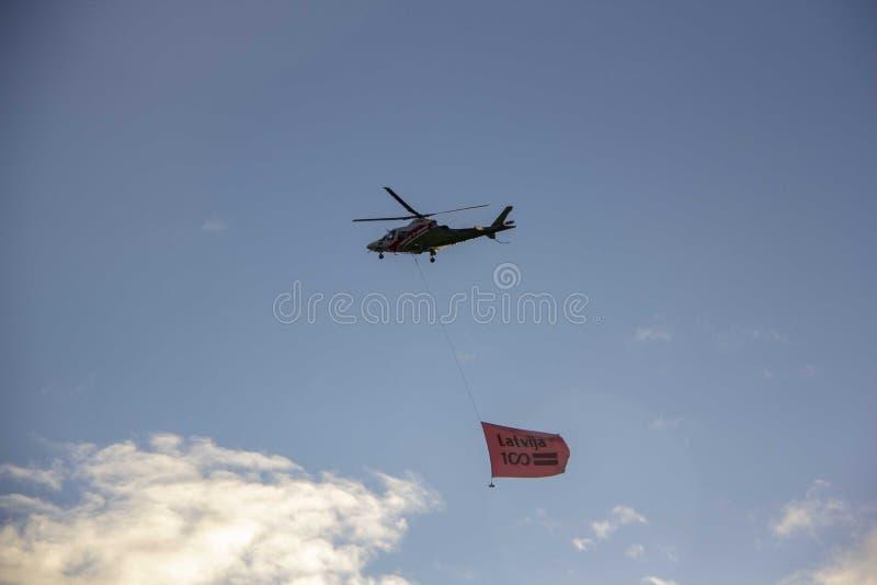 Helicópteros e avião da OTAN com a bandeira na parada militar em Riga, Letónia imagens de stock royalty free