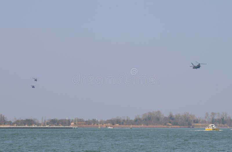 Helicópteros militares en la formación sobre el título veneciano de la laguna hacia la base aérea de Aviano en Italia del noreste fotografía de archivo