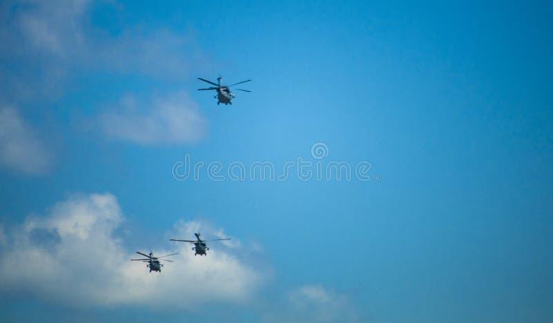 Helicópteros militares que se elevan en el cielo azul fotografía de archivo