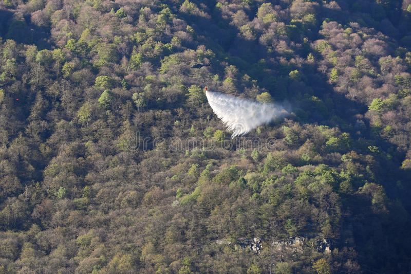 Helicópteros que deixam cair a água no incêndio florestal nas montanhas fotos de stock