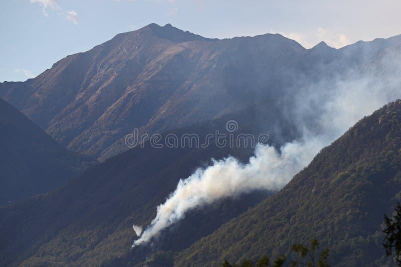 Helicópteros que deixam cair a água no incêndio florestal nas montanhas imagens de stock