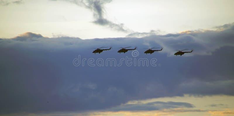 Helicópteros que voam contra o céu de nivelamento no por do sol foto de stock royalty free
