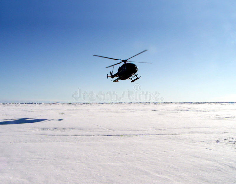 Helicopter in Antarctica. Helicopter landing on field of white snow and ice in Antarctica stock image