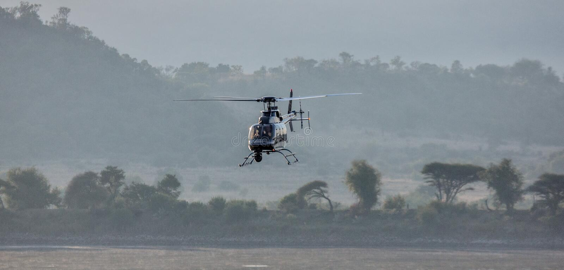 Helicopter - anti poaching unit - Kruger National Park. Anti poaching Helicopter with camera fling over the Kruger National park bush stock image